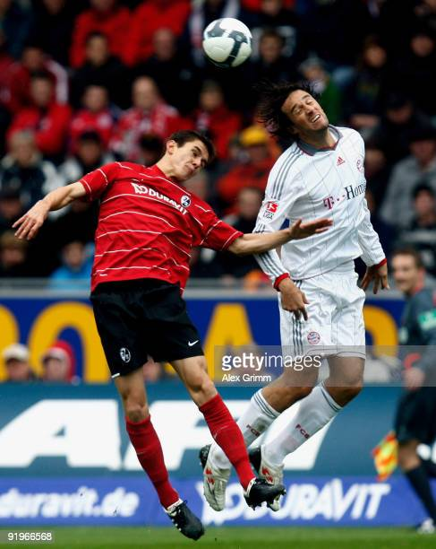 Luca Toni of Muenchen jumps for a header with Johannes Flum of Freiburg during the Bundesliga match between SC Freiburg and Bayern Muenchen at the...