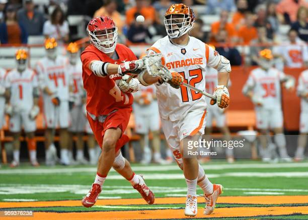 Luca Tria of the Cornell Big Red and Danny Varello of the Syracuse Orange react to a loose ball during a 2018 NCAA Division I Men's Lacrosse...