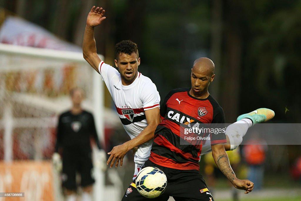 Lucao of Sao Paulo battles for the ball with Dinei of Vitoris during the match between Vitoria and Sao Paulo as part of Brasileirao Series A 2014 at Estadio Manoel Barradas on November 9, 2014 in Salvador, Bahia, Brazil.