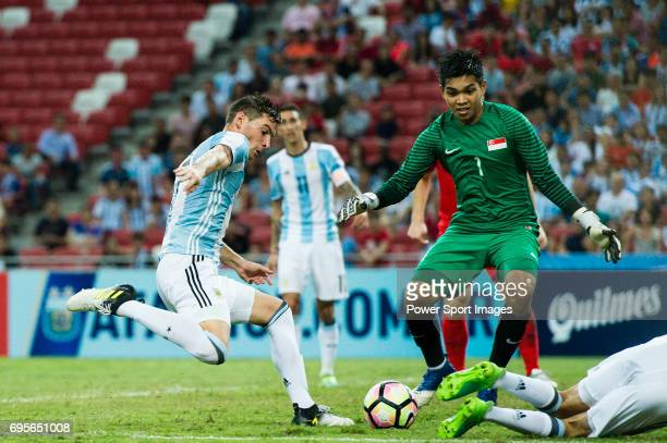 Lucas Alario of Argentina attempts a kick while being defended by Izwan Mahbud of Singapore during the International Test match between Argentina and...