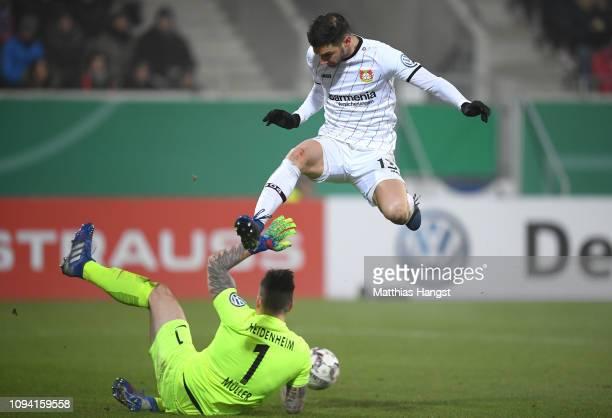 Lucas Alario of Bayer 04 Leverkusen collides with Kevin Mueller of 1.FC Heidenheim 1846 during the DFB Cup match between 1. FC Heidenheim and Bayer...