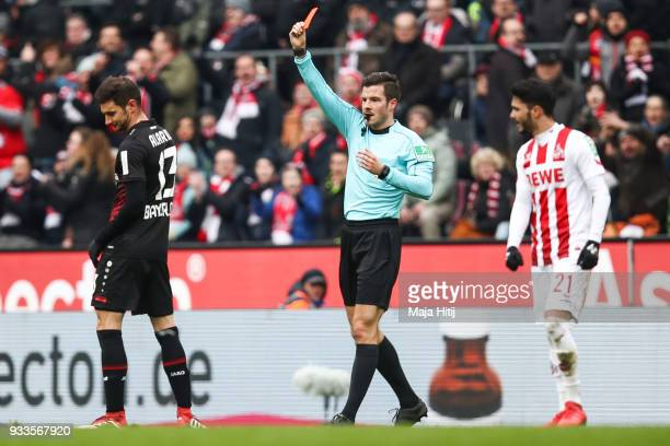 Lucas Alario of Bayer Leverkusen is shown a red card by referee Harm Osmers during the Bundesliga match between 1 FC Koeln and Bayer 04 Leverkusen at...