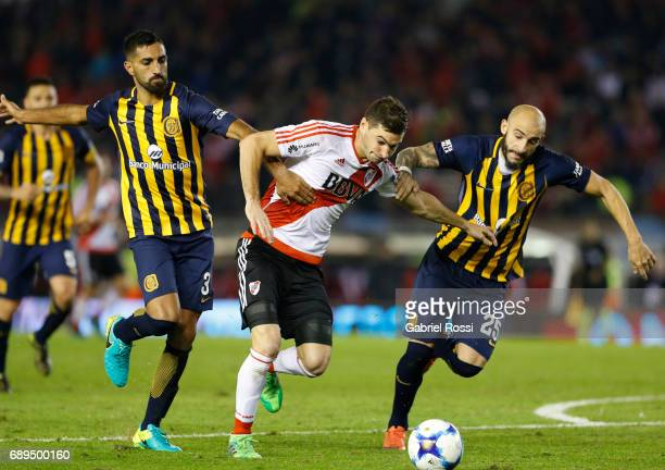 Lucas Alario of River Plate fights for the ball with Hernan Menosse and Javier Pinola of Rosario Central during a match between River Plate and...