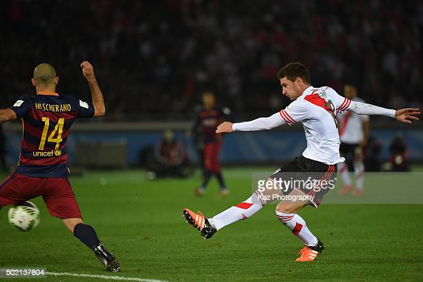 Lucas Alario of River Plate shoots the ball unde the pressure from Javier Mascherano of FC Barcelona during the FIFA Club World Cup Final match...