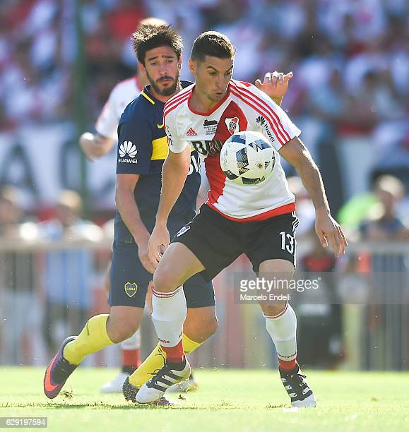 Lucas Alario of River Plate vies for the ball with Pablo Perez of Boca Juniors during a match between River Plate and Boca Juniors as part of Torneo...