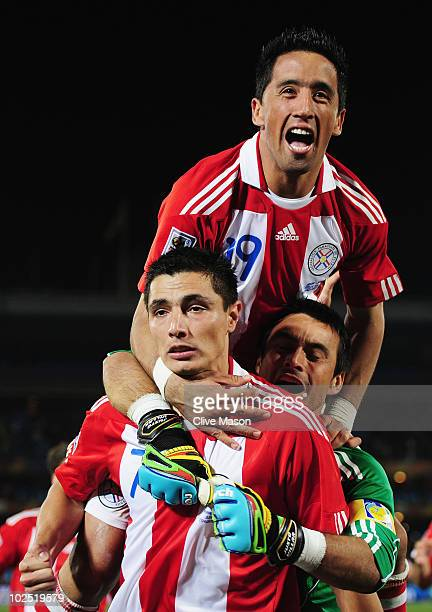 Lucas Barrios and Justo Villar celebrate with Oscar Cardozo of Paraguay after scoring his penalty to win his team a penalty shootout during the 2010...