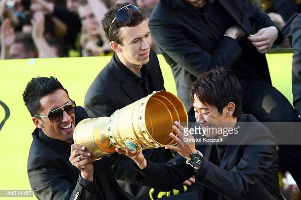 Lucas Barrios and Shinji Kagawa of Dortmund lift the trophy during a parade at Borsigplatz celebrating Borussia Dortmund's Bundesliga and DFB Cup win...