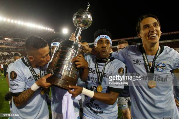 Lucas Barrios Bruno Cortez and Geromel of Gremio celebrate with the trophy after winning the second leg match between Lanus and Gremio as part of...