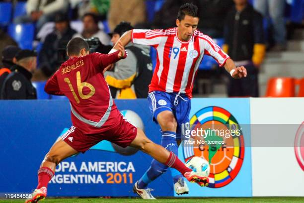 Lucas Barrios from Paraguay fights for the ball against Roberto Rosales from Venezuela during a semi final match between Paraguay and Venezuela at...