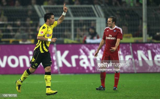 Lucas Barrios of Dortmund celebrates scoring the second goal and Joris Mathijsen looks dejected during the Bundesliga match between Borussia Dortmund...