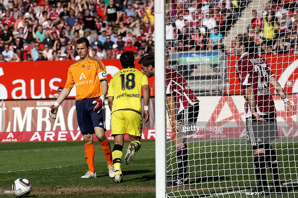 Lucas Barrios (2L) of Dortmund scores his team's third goal as Raphael Schaefer, Dominic Maroh and Javier Pinola (L-R) of Nuernberg react during the Bundesliga match between 1. FC Nuernberg and Borussia Dortmund at the Easy Credit Stadium on April 24, 2010 in Nuremberg, Germany.
