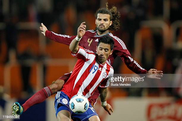 Lucas Barrios of Paraguay struggles for the ball with Oswaldo Vizcarrondo of Venezuela during a match as part of Copa America 2011 Semifinal at...