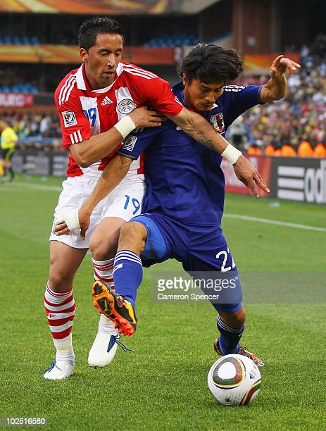 Lucas Barrios of Paraguay tackles Yuji Nakazawa of Japan during the 2010 FIFA World Cup South Africa Round of Sixteen match between Paraguay and...