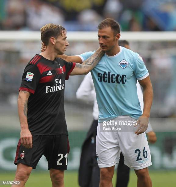 Lucas Biglia of AC Milan and Stefan Radu of SS Lazio react during the Serie A match between SS Lazio and AC Milan at Stadio Olimpico on September 10...