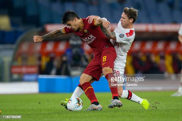 Lucas Biglia of AC Milan challenges Diego Perotti of AS Roma during the Serie A match between AS Roma and AC Milan at Stadio Olimpico on October 27,...