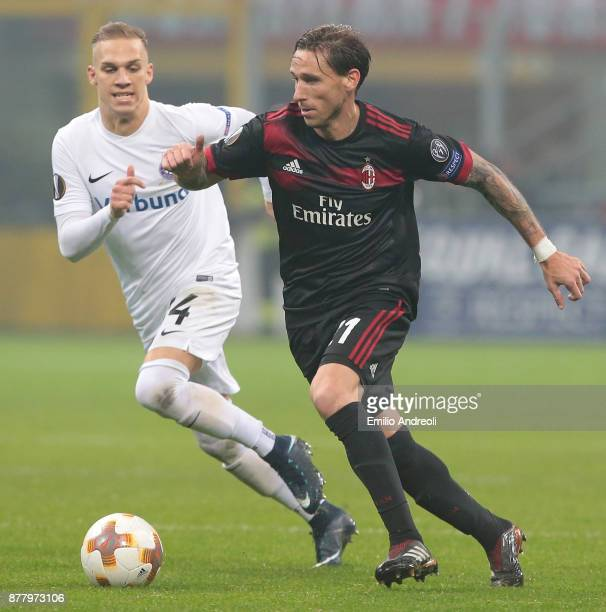 Lucas Biglia of AC Milan competes for the ball with Christoph Monschein of FK Austria Wien during the UEFA Europa League group D match between AC...
