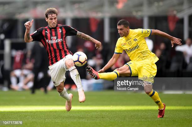 Lucas Biglia of AC Milan competes for the ball with Manuel Pucciarelli of AC ChievoVerona during the Serie A football match between AC Milan and AC...