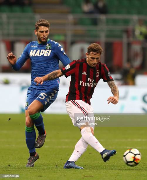 Lucas Biglia of AC Milan is challenged by Domenico Berardi of US Sassuolo during the serie A match between AC Milan and US Sassuolo at Stadio...