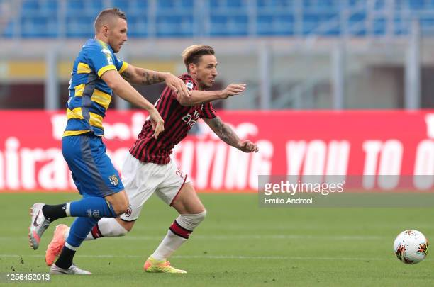 Lucas Biglia of AC Milan is challenged by Jasmin Kurtic of Parma Calcio during the Serie A match between AC Milan and Parma Calcio at Stadio Giuseppe...