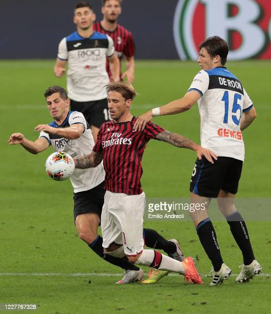 Lucas Biglia of AC Milan is challenged by Remo Freuler and Marten De Roon of Atalanta BC during the Serie A match between AC Milan and Atalanta BC at...