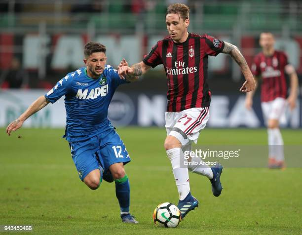 Lucas Biglia of AC Milan is challenged by Stefano Sensi of US Sassuolo Calcio during the serie A match between AC Milan and US Sassuolo at Stadio...