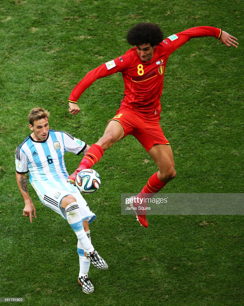 Lucas Biglia of Argentina and Marouane Fellaini of Belgium compete for the ball during the 2014 FIFA World Cup Brazil Quarter Final match between Argentina and Belgium at Estadio Nacional on July 5, 2014 in Brasilia, Brazil.