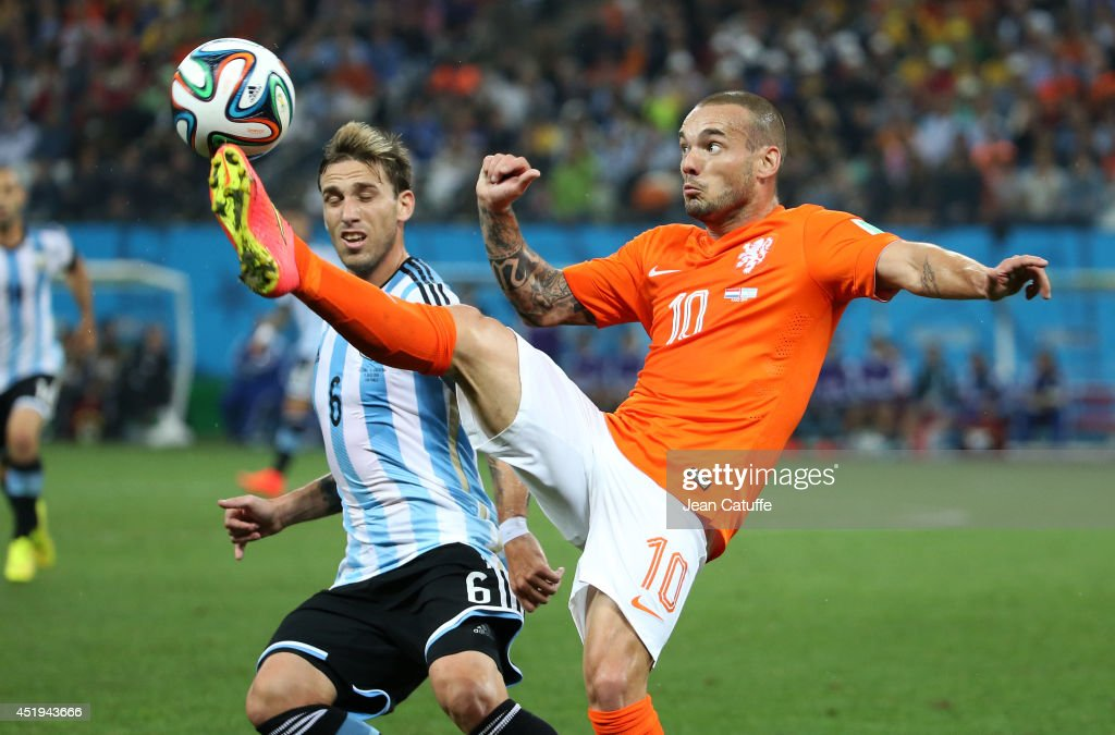 Lucas Biglia of Argentina and Wesley Sneijder of the Netherlands in action during the 2014 FIFA World Cup Brazil Semi Final match between the Netherlands and Argentina at Arena de Sao Paulo on July 9, 2014 in Sao Paulo, Brazil.