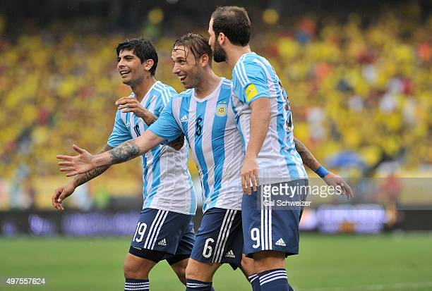 Lucas Biglia of Argentina celebrates with teammates Gonzalo Higuain and Ever Banega after scoring the opening goal during a match between Colombia...