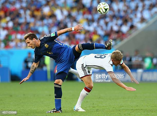 Lucas Biglia of Argentina collides with Toni Kroos of Germany during the 2014 FIFA World Cup Brazil Final match between Germany and Argentina at...