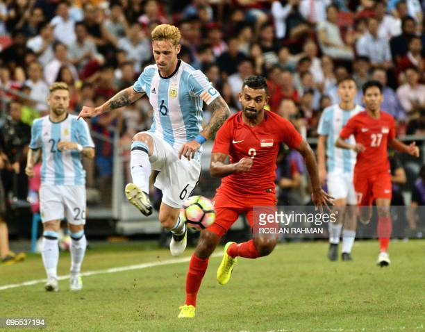 Lucas Biglia of Argentina competes for the ball with Muhammad Nazrul Bin Ahmad Nazari of Singaporeduring their international friendly football...