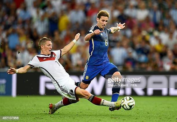 Lucas Biglia of Argentina is tackled by Bastian Schweinsteiger of Germany during the 2014 FIFA World Cup Brazil Final match between Germany and...
