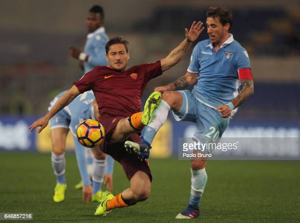 Lucas Biglia of SS Lazio competes for the ball with Francesco Totti of AS Roma during the TIM Cup match between SS Lazio and AS Roma at Olimpico...
