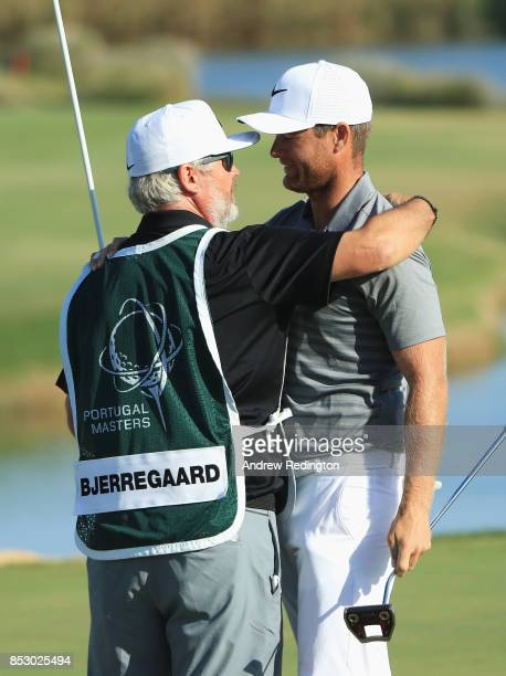 Lucas Bjerregaard of Denmark celebrates victory with his caddie Brian Bo Martin on the 18th green during day four of the Portugal Masters at Dom...