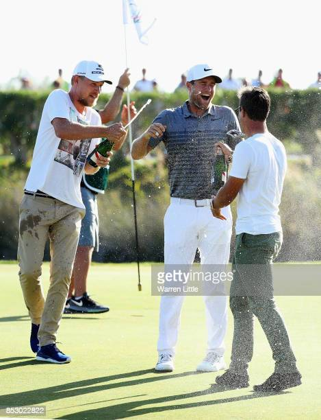Lucas Bjerregaard of Denmark celebrates victory with Jeff Winther and Thorbjorn Olesen on the 18th green during day four of the Portugal Masters at...