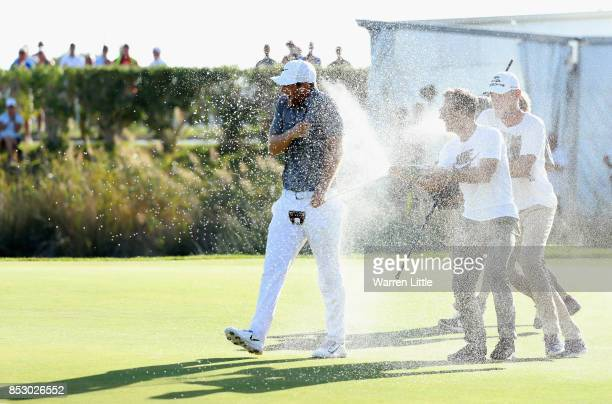Lucas Bjerregaard of Denmark is sprayed with champagne by Jeff Winther and Thorbjorn Olesen on the 18th green after his victory during day four of...