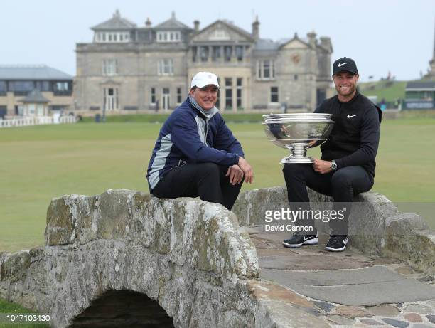 Lucas Bjerregaard of Denmark sits on the Swilcan Bridge with the trophy with his amateur partner Dan Friedkin of the United States after his one shot...