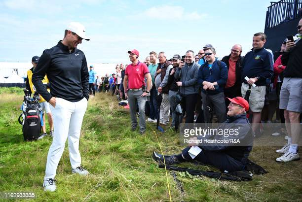 Lucas Bjerregaard of Denmark speaks with a spectator 'sitting' on his ball on the first hole during the second round of the 148th Open Championship...