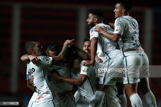 Lucas Braga of Santos celebrates with teammates after scoring the first goal of his team during a third round first leg match between San Lorenzo and...
