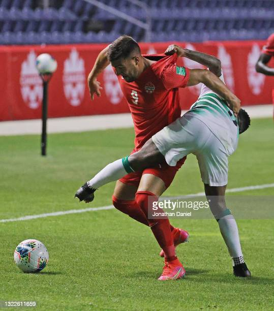 Lucas Cavallini of Canada battles with Ridgeciano Haps of Suriname during a FIFA World Cup Qualifier at SeatGeek Stadium on June 08, 2021 in...