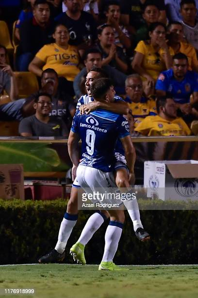 Lucas Cavallini of Puebla celebrates with teammates after scoring his team's first goal during the 11th round match between Tigres UANL and Puebla as...