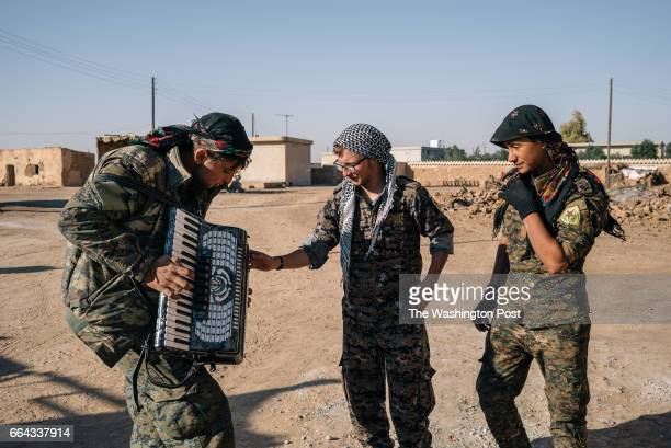 Lucas Chapman an American volunteer with the YPG watches as a YPG fighter plays an accordion in a rear base near Tal Samin Syria