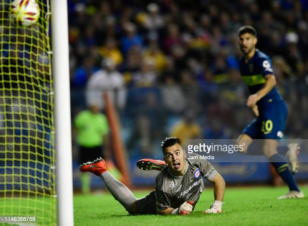 Lucas Chaves of Argentinos Juniors looks the ball as Lisandro Lopez of Boca Juniors celebrates after scoring his side's first goal during a second...