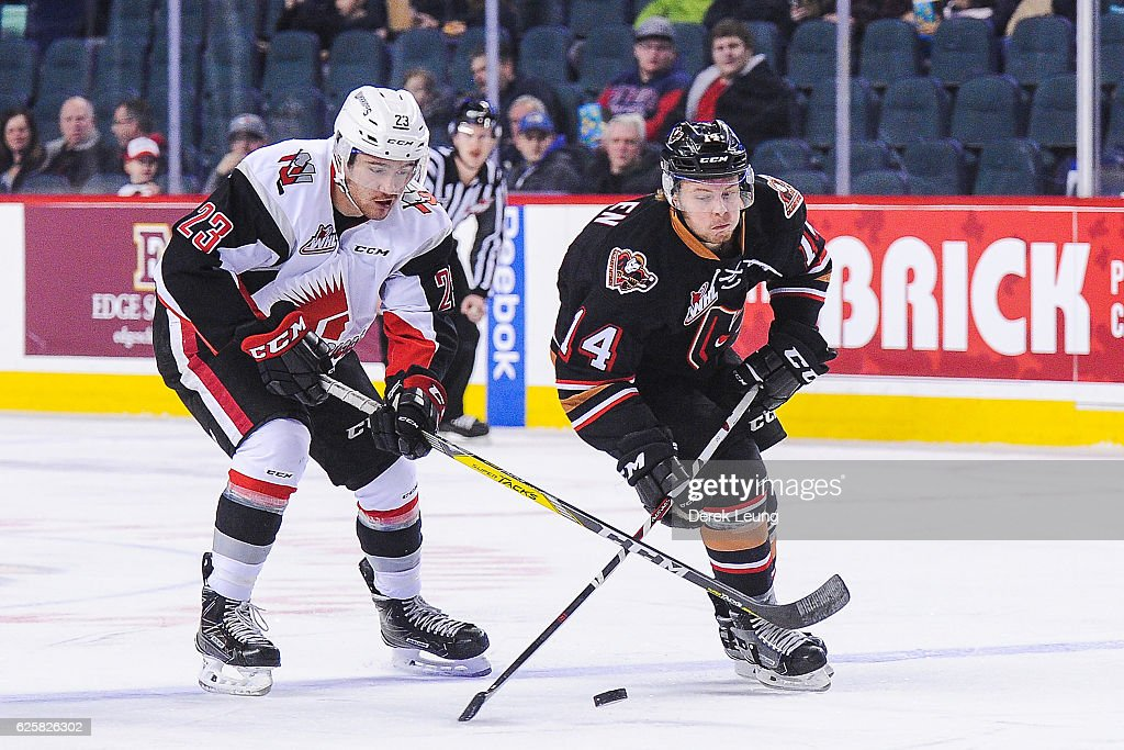 Lucas Cullen #14 of the Calgary Hitmen fights for the puck against Tristin Langan #23 of the Moose Jaw Warriors during a WHL game at Scotiabank Saddledome on November 25, 2016 in Calgary, Alberta, Canada.