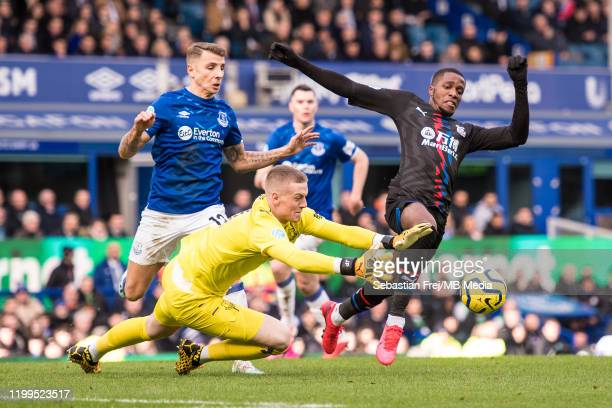 Lucas Digne and Jordan Pickford of Everton FC and Wilfried Zaha of Crystal Palace in action during the Premier League match between Everton FC and...