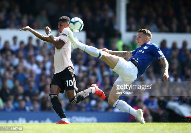 Lucas Digne of Everton clears from Marcus Rashford of Manchester United during the Premier League match between Everton FC and Manchester United at...