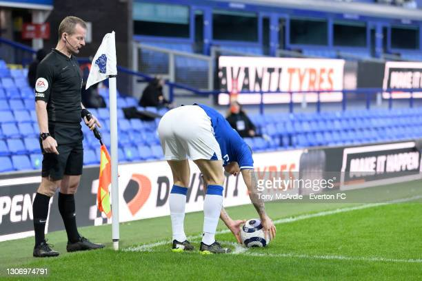 Lucas Digne of Everton is watched by the assistantships referee linesman as he prepares to take a corner during the Premier League match between...