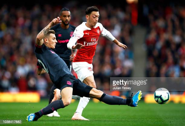 Lucas Digne of Everton tackles Mesut Ozil of Arsenal during the Premier League match between Arsenal FC and Everton FC at Emirates Stadium on...