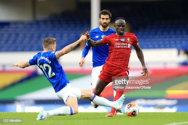 Lucas Digne of Everton tackles Sadio Mane of Liverpool during the Premier League match between Everton FC and Liverpool FC at Goodison Park on June...