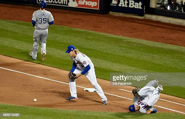 Lucas Duda and Noah Syndergaard of the New York Mets get tangled up at first trying to tag Eric Hosmer of the Kansas City Royals during Game 3 of the...