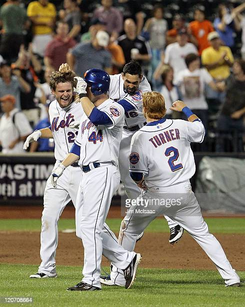 Lucas Duda of the New York Mets celebrates his walk off two-run ninth inning single against the San Diego Padres with teammates Justin Turner, Angel...